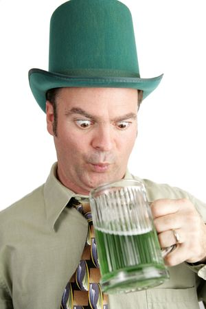 Man on St. Patricks Day looking into his glass of green beer with anticipation.  White background. photo