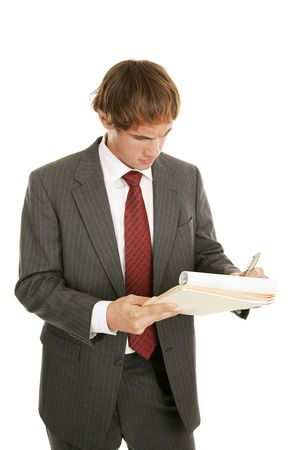 graduation suit: Handsome young businessman working out a problem on a notepad.  Isolated on white.   Stock Photo