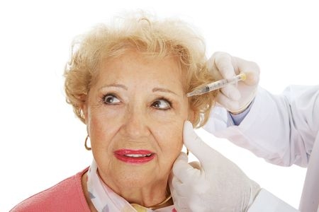 fill in: Senior woman having cosmetic surgery injections to fill in wrinkles around eyes.  White background.
