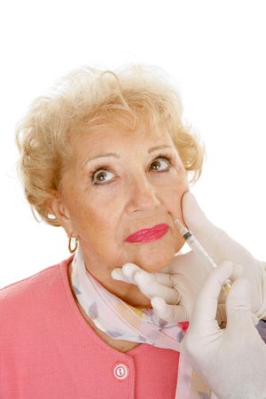 Senior woman getting cosmetic injections in the wrinkles around her mouth.  White background.   photo