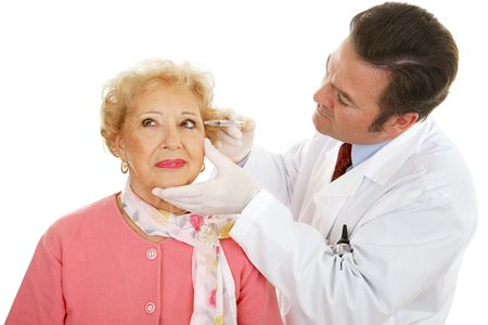 Cosmetic surgeon injecting a senior woman's face to fill in wrinkles.  Isolated on white.