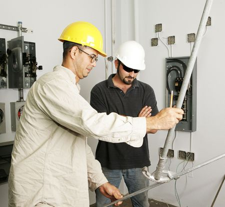 according: Electrician and foreman bending pipe for a job.  Actual electricians working according to industry safety and code standards.  (markings on bender are instructional not trademarked) Stock Photo