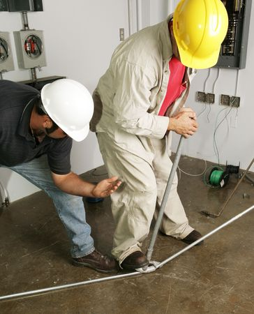 instructional: An electrician bending pipe as his foreman looks on and offers guidance.  Actual electricians working according to industry safety and code standards. (writing on bender is instructional not trademark)