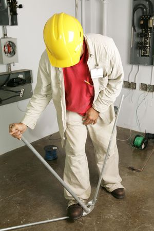 steel toe boots: Electrician bending conduit pipe.  Actual electrician performing work according to industry code and safety standards.  (writing on pipe is instructional, not trademark) Stock Photo