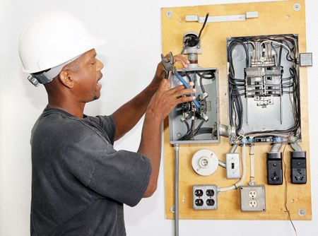wire: Electrician crimping a wire in an electrical panel.  Model is actual electrician performing work according to industry code and safety standards.