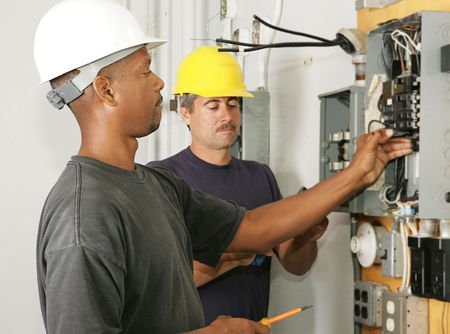 electrical panel: An african american and a caucasian electrician working on a panel.  Actual electricians performing work according to industry safety and code standards.