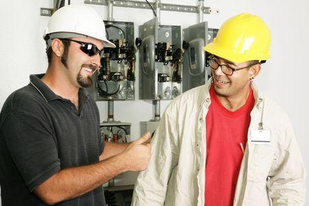 meter box: El�ctrica capataz dando un trabajador el dedo pulgar hacia arriba. Los modelos son reales electricistas.  Foto de archivo
