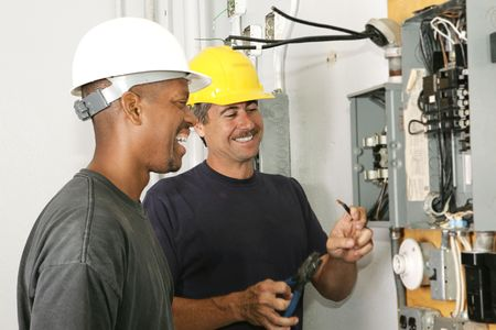 energy work: Two electricians working on an electrical panel together.  Actual electricians performing work according to industry code and safety standards.