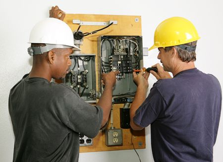 Electricians repairing breaker panel.  Actual electricians performing work according to industry safety and code standards.   Stock Photo - 2392179