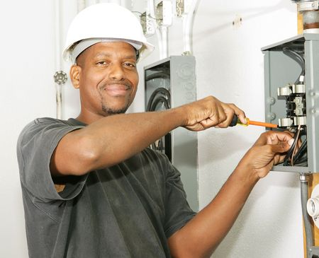 Handsome african american electrician working on a breaker panel.  Model is an actual electrician performing work according to industry safety and code standards.