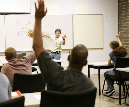 teaching adult: Adult education class raising hands to ask questions.