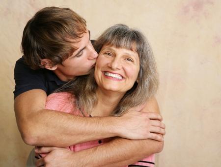 madre soltera: Joven adulto  adolescente tard�o hijo besar a su madre en la mejilla.  Foto de archivo