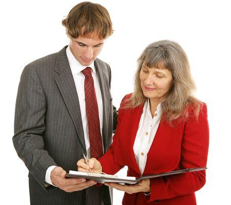 female boss: Weiblicher Chef, der mit einem Report erzeugt von einem jungen Gesch�ftsmann einverstandenIST. Lokalisiert auf Wei�.