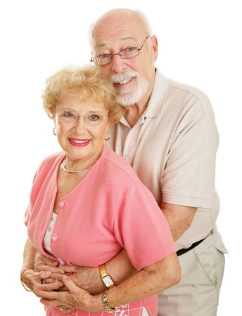 Happy, attractive senior couple wearing glasses.  Vertical view isolated on white.