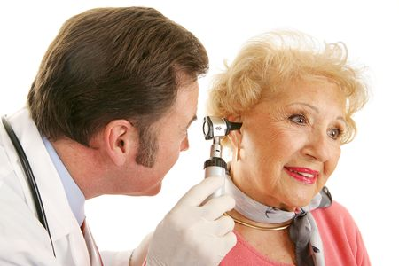 otoscope: Doctor using otoscope to look inside a beatiful senior womans ears.  Isolated on white.