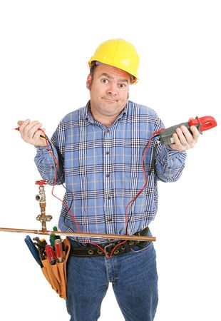 journeyman technician: Electrician confused by a plumbing project.  Hes holding a voltage meter which is useless on a plumbing pipe.  Isolated on white. Stock Photo