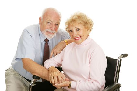 Attractive senior couple - the wife is in a wheelchair.  Isolated on white.   photo
