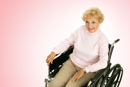 Pretty senior woman with positive attitude in a wheelchair.  Pink background with room for text.