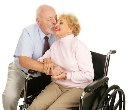 Affectionate senior husband giving his disabled wife a kiss on the cheek.  Isolated on white.   photo