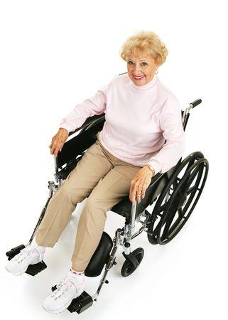 handicap: Bello, ottimista senior signora in una sedia a rotelle. Corpo pieno isolato su bianco.