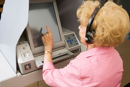 impaired: Senior lady using headphones for hearing impaired and voting on touch screen machine.   Stock Photo