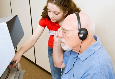 instructing: Young election volunteer explaining the new touch screen voting machine to a vision impaired man in Florida.  Stock Photo