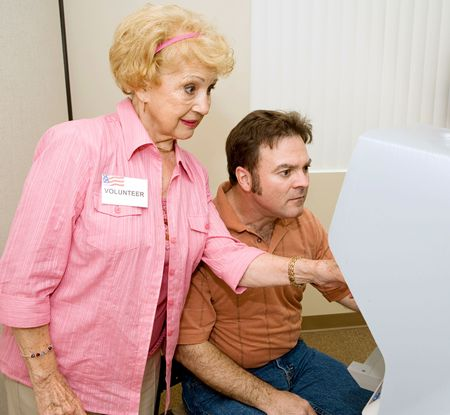 local election: Senior woman volunteer explaining new voting machine to voter.