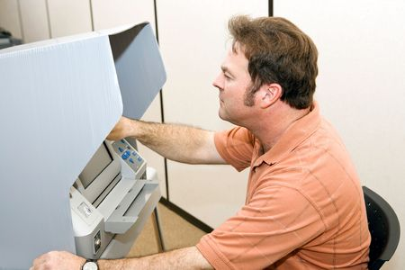 voting: Man casting his ballot on a touch screen voting machine.
