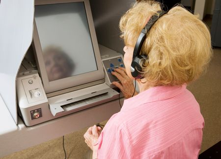 blind people: Senior woman voting in braille on a touch screen machine for vision impaired.   Stock Photo