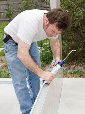 caulking: Handyman using a caulking gun to caulk a home improvement project.   Stock Photo