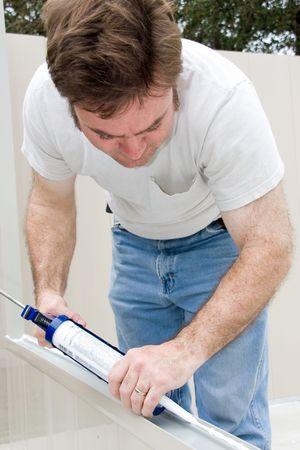 caulking: Handyman using a caulking gun to caulk a window.   Stock Photo