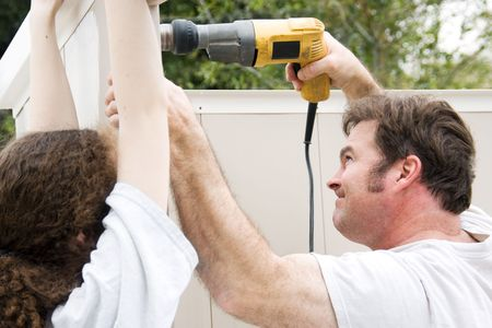 Father and daughter working on home improvement project.  Hes using the drill.   photo