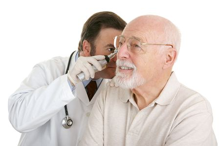 otoscope: Senior man having his ears checked at the doctors office.  Isolated on white.