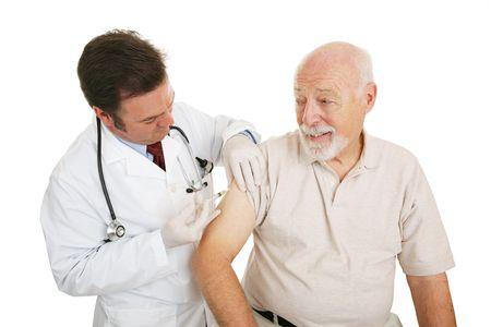 vacunaci�n: Senior hombre obtener una vacuna contra la gripe de su m�dico. Aislado en blanco.  Foto de archivo
