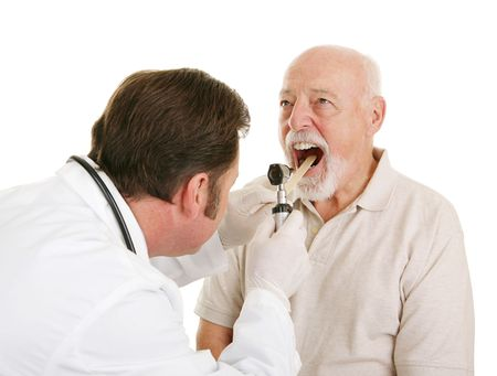 inconvenience: Doctor using a tongue depressor and an otoscope to look inside a senior patients mouth.  Isolated on white.