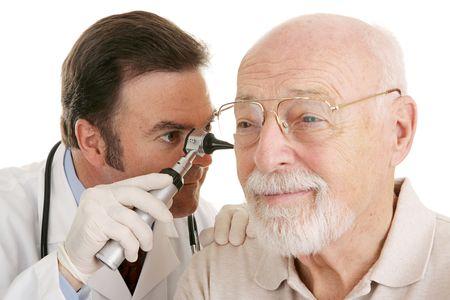 physical test: Aggiusti usando il otoscope per osservare in orecchi dei man dellanziano. Primo piano su bianco. Fuoco sul medico.