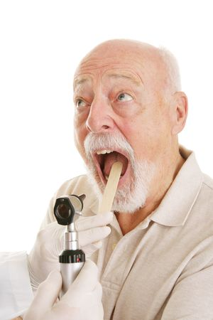 inconvenience: Senior man opening his mouth for the doctor to look in his throat.  White background. Stock Photo