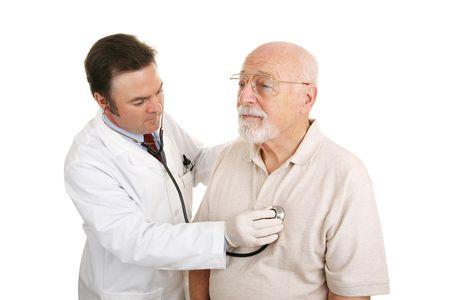 医者はシニア患者の心拍音を聞きます。白で隔離されます。