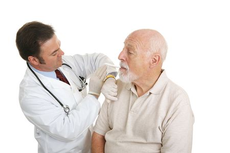 Doctor taking a senior man's temperature during a routine physical.  Isolated on white.   Stock Photo - 2576477