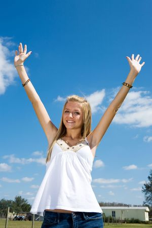 Beautiful blond teen girl outdoors raising her arms in freedom. Stock Photo - 2607666