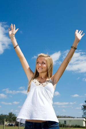 Blond teen girl outdoors raising her arms in praise.   Stock Photo - 2607665