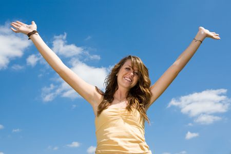 Beautiful teen girl raising her hands in joy and praise against a blue sky. photo