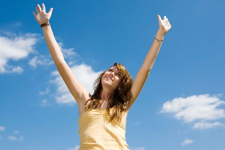 Beautiful teen girl raising her arms and looking to heaven in praise.