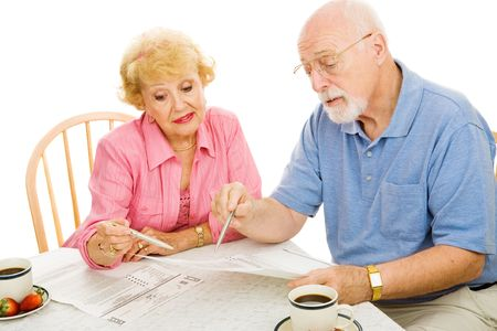 Senior couple filling out their absentee ballots at home.  Isolated on white.