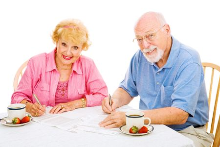 Senior couple filling out their absentee ballots for upcoming election.  Isolated on white.   photo