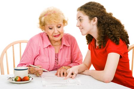 absentee: Senior woman filling out absentee ballot with help of her granddaughter.  Isolated on white. Stock Photo