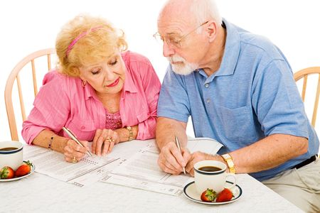 absentee: Senior couple filling out their absentee ballots together.  Isolated on white.   Stock Photo