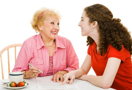 absentee: Senior grandmother and teen grandmother discussing democracy together and filling out absentee ballot.  Isolated on white.