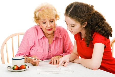 absentee: Teen girl helping her grandmother read the fine print on the absentee ballot.  Isolated on white. Stock Photo