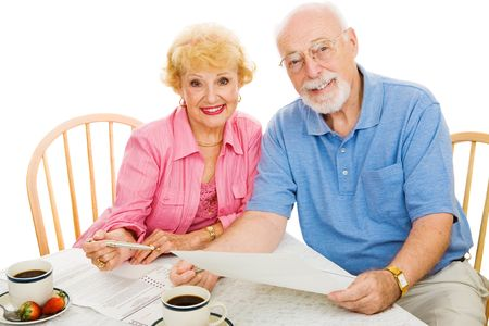 absentee: Senior couple using absentee ballots to vote in an election.  Isolated on white. Stock Photo